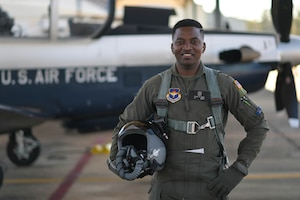U.S. Air Force 2nd Lt. Clifford Mua, 41st Flying Training Squadron student pilot, stands in front of a T-6 Texan II before flight Nov. 4, 2020, on Columbus Air Force Base Miss. Mua completed his dollar ride, the first flight a student pilot takes during Specialized Undergraduate Pilot Training, and in keeping with tradition, presented his instructor pilot a decorated dollar after the flight was complete. (U.S. Air Force photo by Senior Airman Jake Jacobsen)