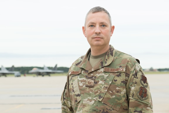 An Airman poses for a photo on the flight line