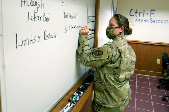U.S. Air Force Tech. Sgt. Kathy Pool, 335th Training Squadron Personnel Apprentice Course instructor, writes class material on a whiteboard inside Wolfe Hall at Keesler Air Force Base, Mississippi, November 3, 2020. The 335th TRS tested the Direct to Duty Technical Training program on a class of prior-service students, aiming to save money and time, keep the students safe and healthy and allow them to stay with their families. (U.S. Air Force photo by Airman 1st Class Seth Haddix)