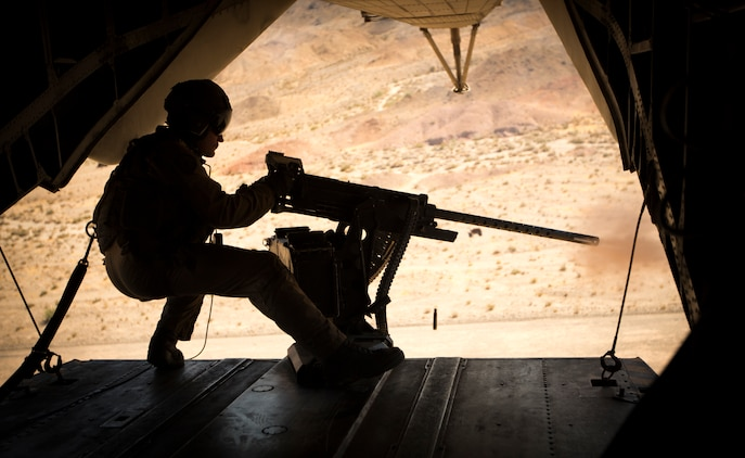 U.S. Marine Corps Staff Sgt. Brandon Mote, a crew chief with Marine Heavy Helicopter Squadron 466, Marine Aviation Group 16, 3rd Marine Aircraft Wing, participates in the Weapons and Tactics Instructor (WTI) course 1-21, while firing an M2 .50-caliber machine gun from a CH-53E Super Stallion in Yuma, Arizona, Oct. 3, 2020.