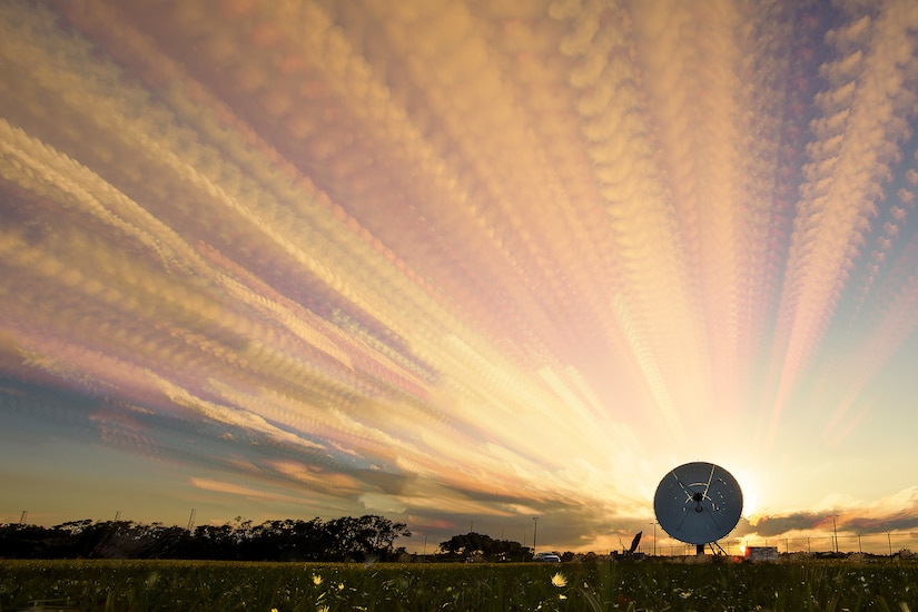 Pinkish rays of light extend skyward from a satellite in a field.