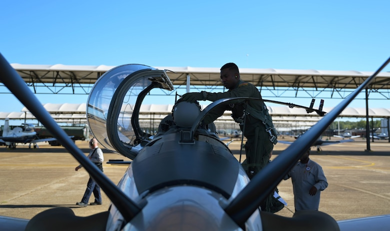 U.S. Air Force 2nd Lt. Clifford Mua, 41st Flying Training Squadron student pilot, places his helmet on the aircraft before stepping inside the cockpit of a T-6 Texan II Nov. 4, 2020, on Columbus Air Force Base Miss. Mua, originally from the Republic of Cameroon, came to the U.S., by winning a diversity visa lottery allowing him to immigrate here on a green card visa before eventually gaining his U.S. citizenship. (U.S. Air Force photo by Senior Airman Jake Jacobsen)