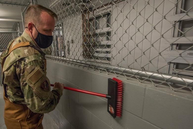Airman scrubs brick wall