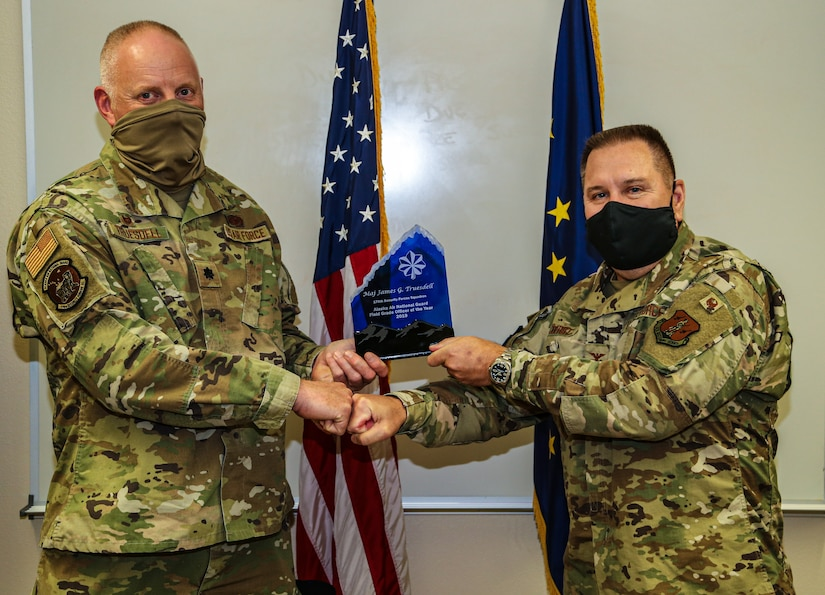 Col. John Oberst, director of staff for the Alaska Air National Guard, presents the Alaska Air Guard award for 2019 Field Grade Officer of the Year to Lt. Col. James Truesdell, the commander of the 176th Security Forces Squadron for his leadership accomplishments in 2019 at the 176th Wing Headquarters on Joint Base Elmendorf-Richardson, Sept. 15, 2020. Truesdell is also a retired Alaska State Trooper. He played a pivotal role in the success of his unit's deployment to Afghanistan in 2019 in support of Operation Enduring Freedom. (U.S. Army National Guard photo by Sgt. Seth LaCount/Released)