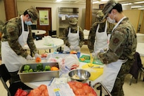 (From left to right) Alaska Air National Guardsmen Tech Sgt. Brayden Van Bevera, Airman 1st Class Fionna Kelty, Tech Sgt. Allen Wilson and Senior Airman Alex Choi, all members of the 176th Force Support Flight Sustainment Services, cut fresh produce at the Five Loaves, Two Fish Kitchen in Wasilla, Alaska, Sept. 25, 2020. Food preparation is one of the many steps in creating quality meal packages for local Alaska residents in need. The Airmen have been volunteering at the kitchen since mid-August, preparing an average of 150 meals per week for local non-profit organizations. (U.S. Army National Guard photo by Sgt. Seth LaCount/Released)