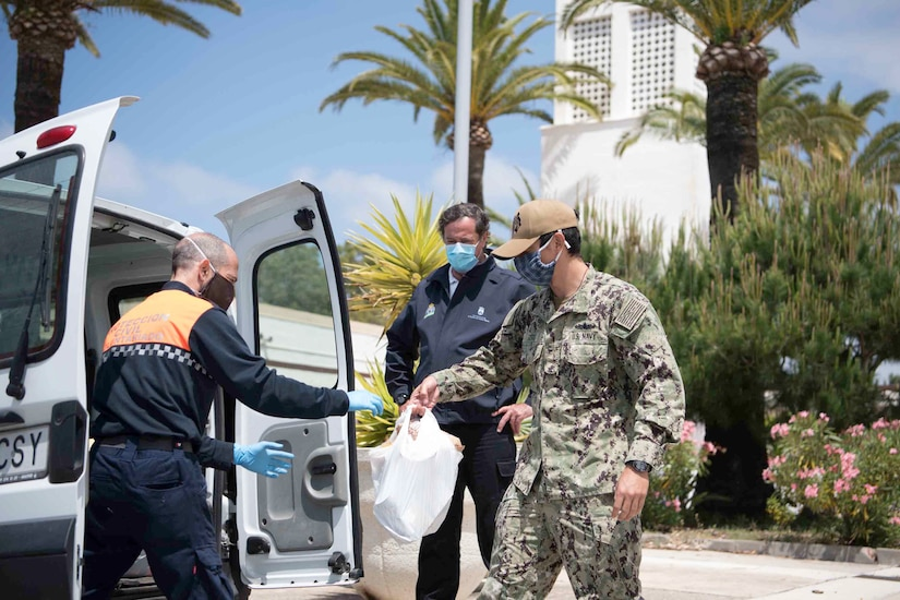 A sailor passes donations to a Spanish official.