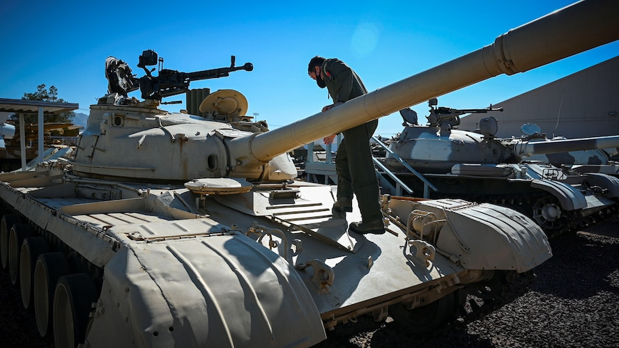 Foreign Liaison Officer climbs onto tank.