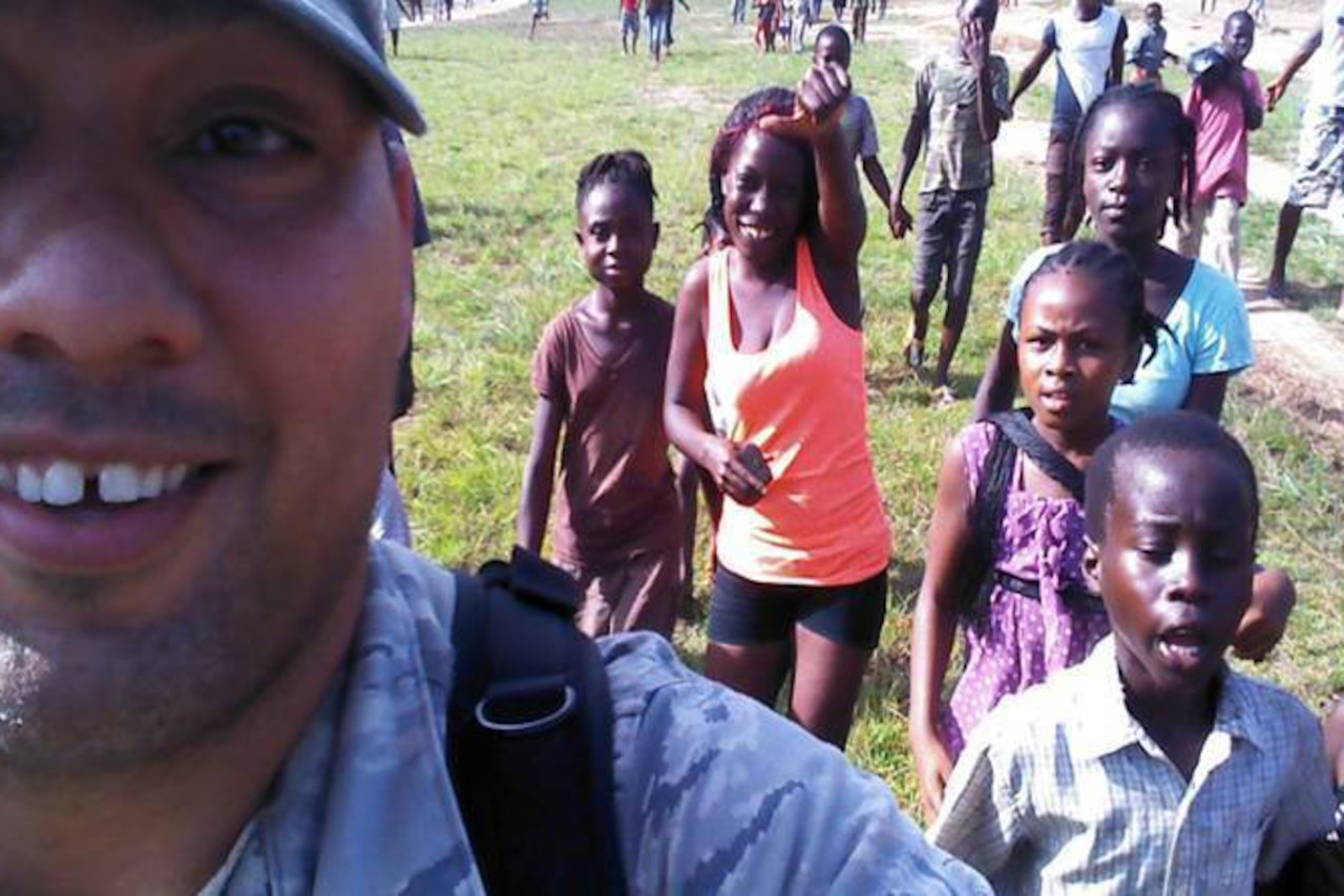 An airman takes a selfie with children.