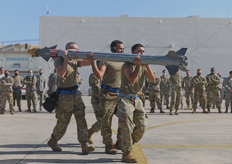 Airmen carry munition.