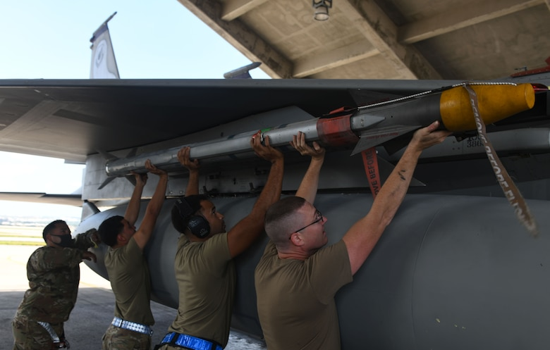 Airmen load a munition.