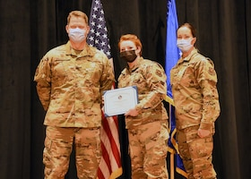 Colonel Peter Bonetti, 90th Missile Wing Commander, and Command Chief Master Sgt. Tiffany Bettisworth, present an Airman Leadership School graduate with a certificate Nov. 5 at the Base Theater on F. E. Warren Air Force Base, Wyo.