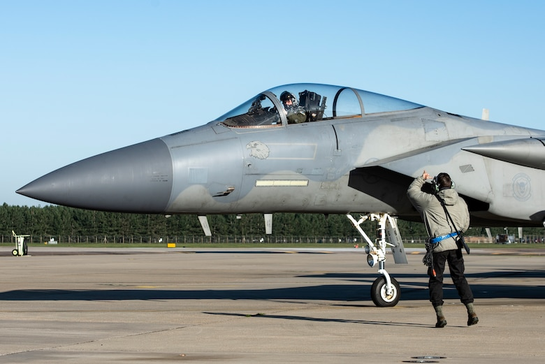 U.S. Air Force Airman 1st Class Tyler Thomas, 492nd Aircraft Maintenance Squadron crew chief, clears an F-15C Eagle for take off in support of exercise Crimson Warrior, at Royal Air Force Lakenheath, England, Nov. 4, 2020. Multi-domain integration exercises like Crimson Warrior strengthen NATO interoperability and test high-end capabilities in a contested, degraded, and operationally limited environment. (U.S. Air Force photo by Airman 1st Class Jessi Monte)