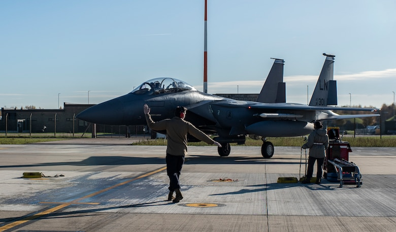 A crew chief assigned to the 48th Aircraft Maintenance Unit marshalls an F-15E Strike Eagle onto the apron after a training sortie in support of exercise Crimson Warrior at Royal Air Force Lakenheath, England, Nov. 6, 2020.  Multi-domain integration exercises like Crimson Warrior strengthen NATO interoperability and test high-end capabilities in a contested, degraded, and operationally limited environment. (U.S. Air Force photo by Airman 1st Class Jessi Monte)