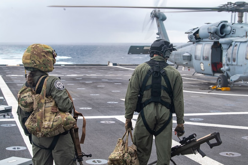 Two people in flight suits walk on a ship's flight deck.