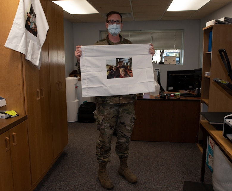 A sergeant picks up a pillow case that has a family picture placed on the pillow.