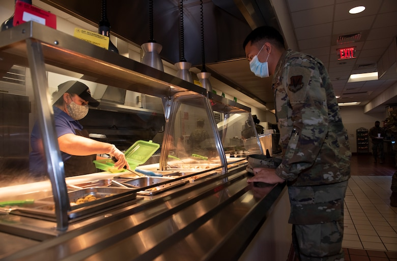 A worker gives a to-go plate, filled with food inside, to an Airman.