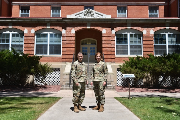 Servicemembers stand in front of 20 AF headquarters.