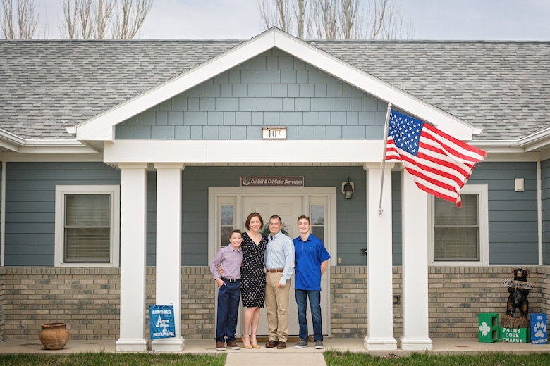 A family stands in front of their house.