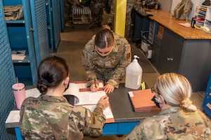 Airmen processing mobility folders.