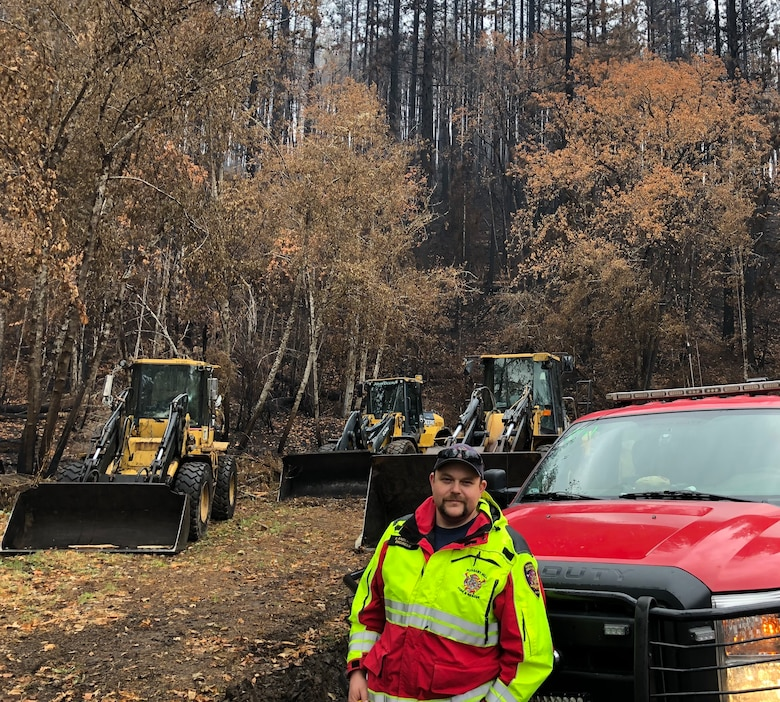 Kyle Anderson stands in front of equipment used to clear debris from highways and side roads caused by the Holiday Farm wildfire.