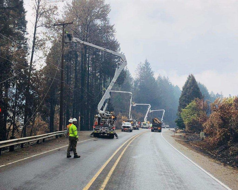 Following the Holiday Farm wildfire, linemen take down power lines so fallers can go in and remove hazardous trees and limbs without causing extra damage to the lines or poles.