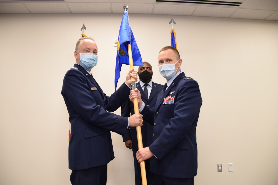 Col. Michael C. Brice, 433rd Medical Group commander, presents the 433rd Aeromedical Staging Squadron unit guidon to Col. David P. Bailey during an assumption of command ceremony Nov. 7, 2020 at Joint Base San Antonio-Lackland, Texas. The ceremony was held at the 433rd Medical Group building. (U.S. Air Force photo by Tech. Sgt. Iram Carmona)
