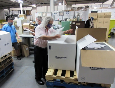 Masked warehouse workers inspect boxes of hand sanitizer stacked on a pallet