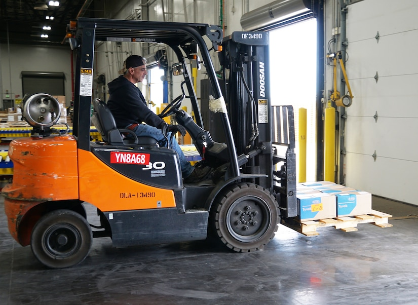 A forklift operator moves a pallet of gowns in a warehouse