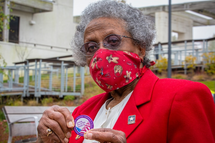 An older woman in a mask holds up a coin.