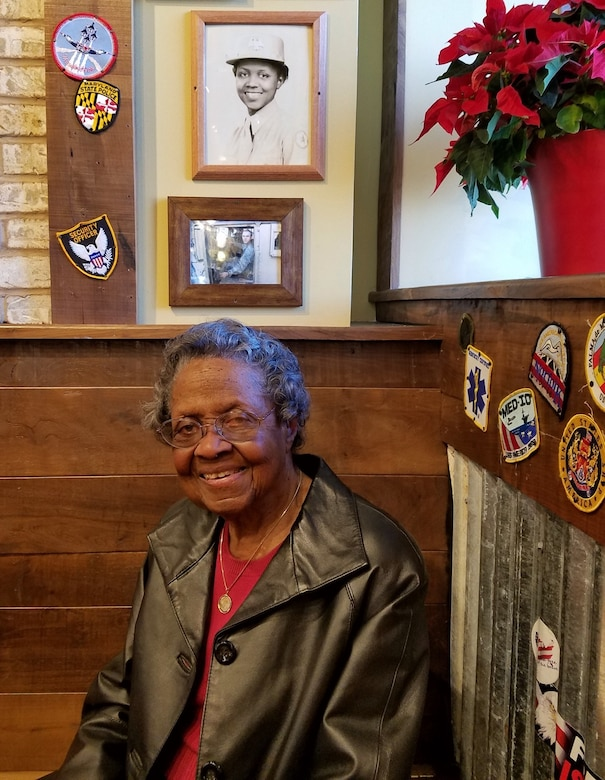 A smiling elderly woman sits in a booth. Photos are on the wall above her.