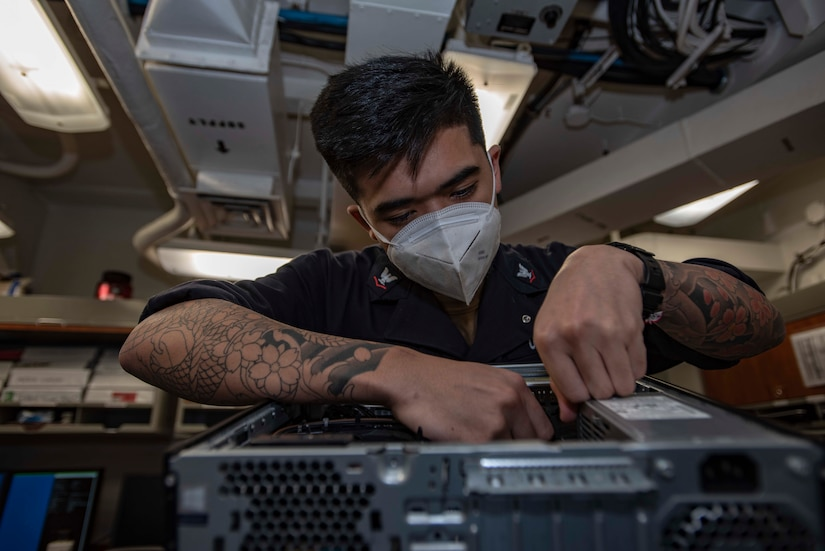 A sailor does maintenance work on a computer.
