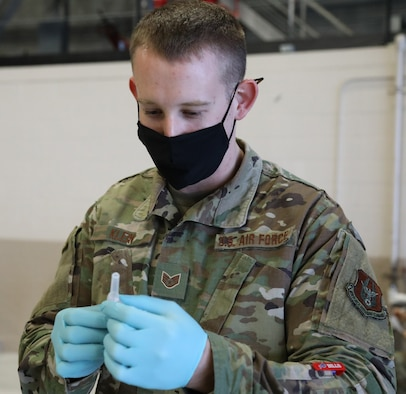U.S. Air Force Staff Sgt. Shayne Klein, an aerospace medical technician with the 446th Aerospace Medicine Squadron here, puts a needle on a flu shot vaccine Nov. 8, 2020.