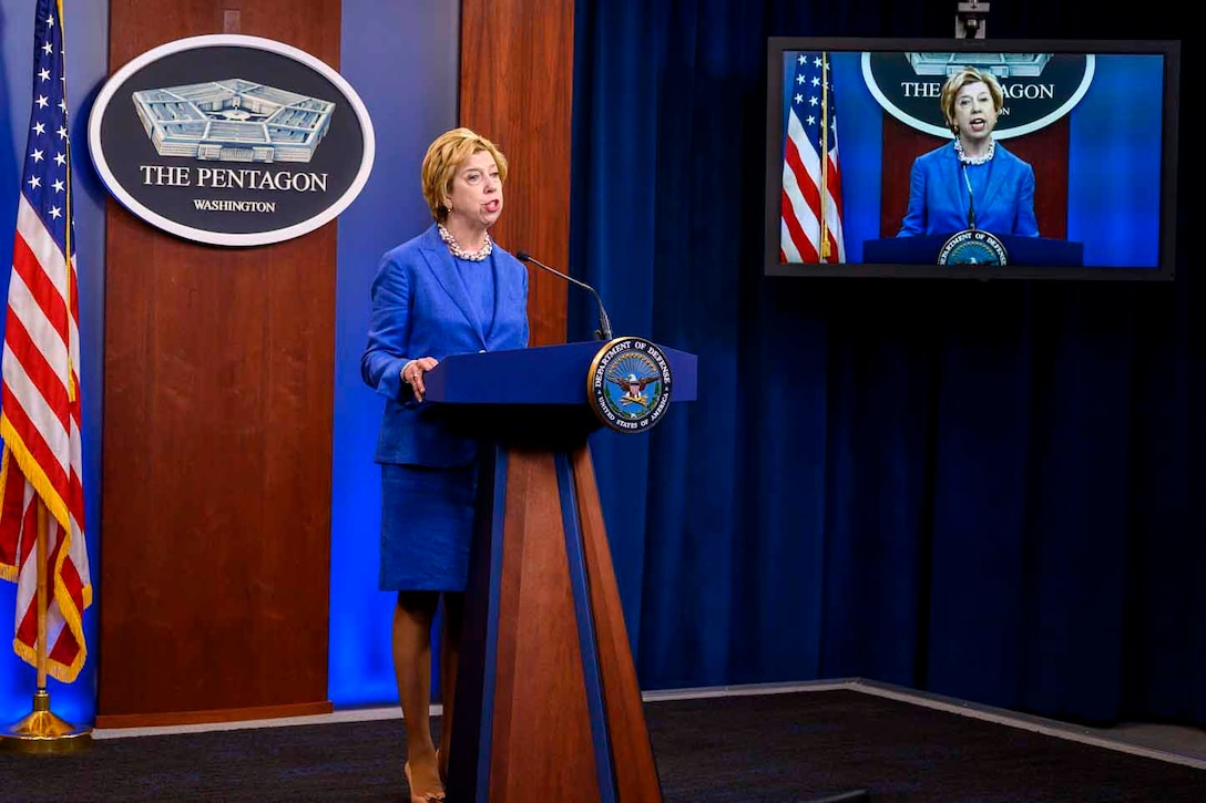 A woman in a blue suit stands at a lectern and speaks to a virtual audience. A sign behind her indicates that she is speaking from the Pentagon.