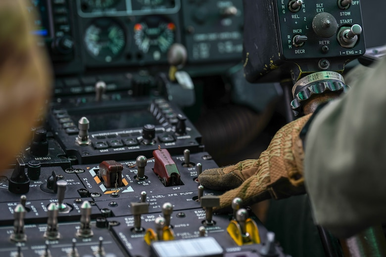 Pilot adjusts UH-1N Iroquois helicopter controls while flying.