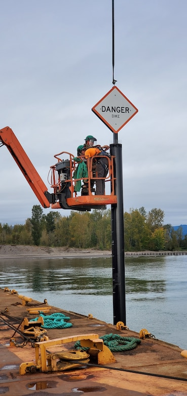 Workers installing a king pile marker warning sign