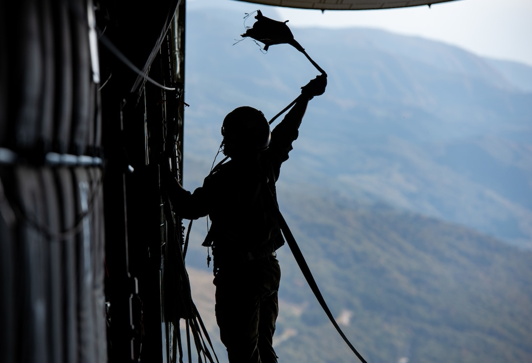 Staff Sgt. Vincenzo Gallegos, 36th Airlift Squadron loadmaster, retrieves a parachute line during a cargo drop during Keen Sword 21