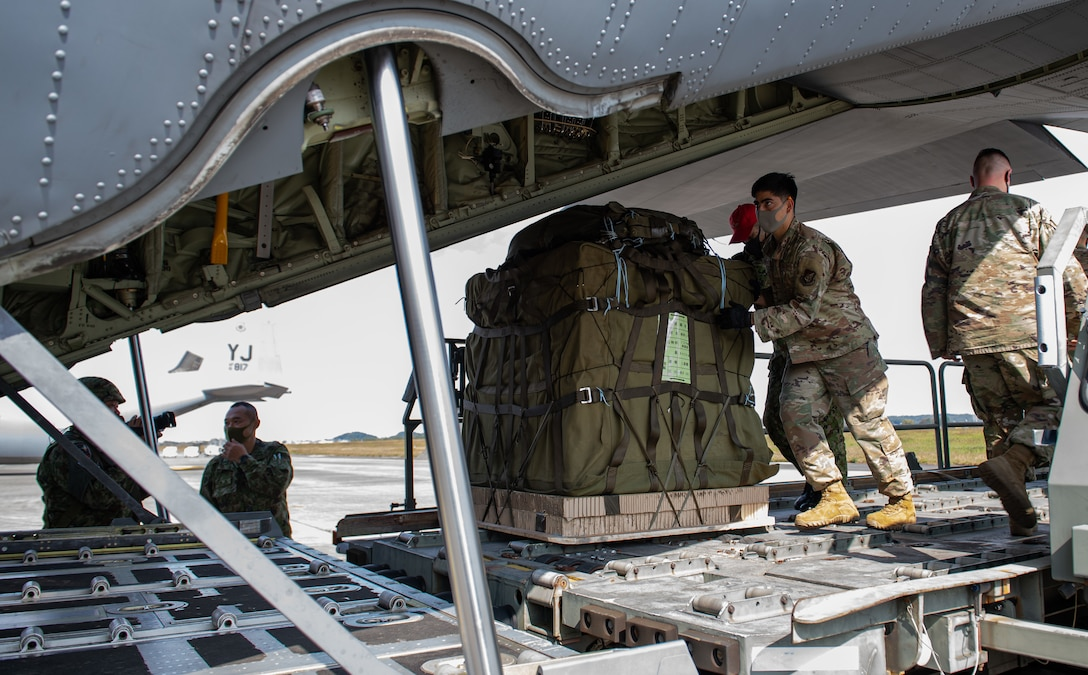 A Japan Self-Defense Forces member, center left, and a 374th Logistics Readiness Squadron Airman, center right, push a containerized delivery system bundle onto a C-130J Super Hercules