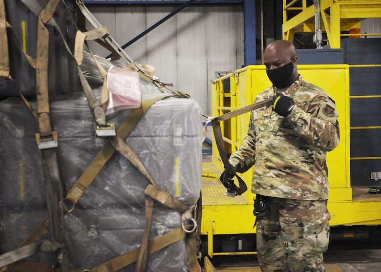 Staff Sgt. Dylan Lewis-Lee, 87th Aerial Port Squadron ramp operations specialist, tightens the net on a training pallet during the 87th Aerial Port Squadron's semi-annual Port Dawg Challenge Oct. 17, 2020. Cargo is prepared for military airlift using strict guidelines based on weight, height, shape and transportation priority, so Port Dawgs must be proficient in numerous methods of securing cargo with nets, chains and straps.