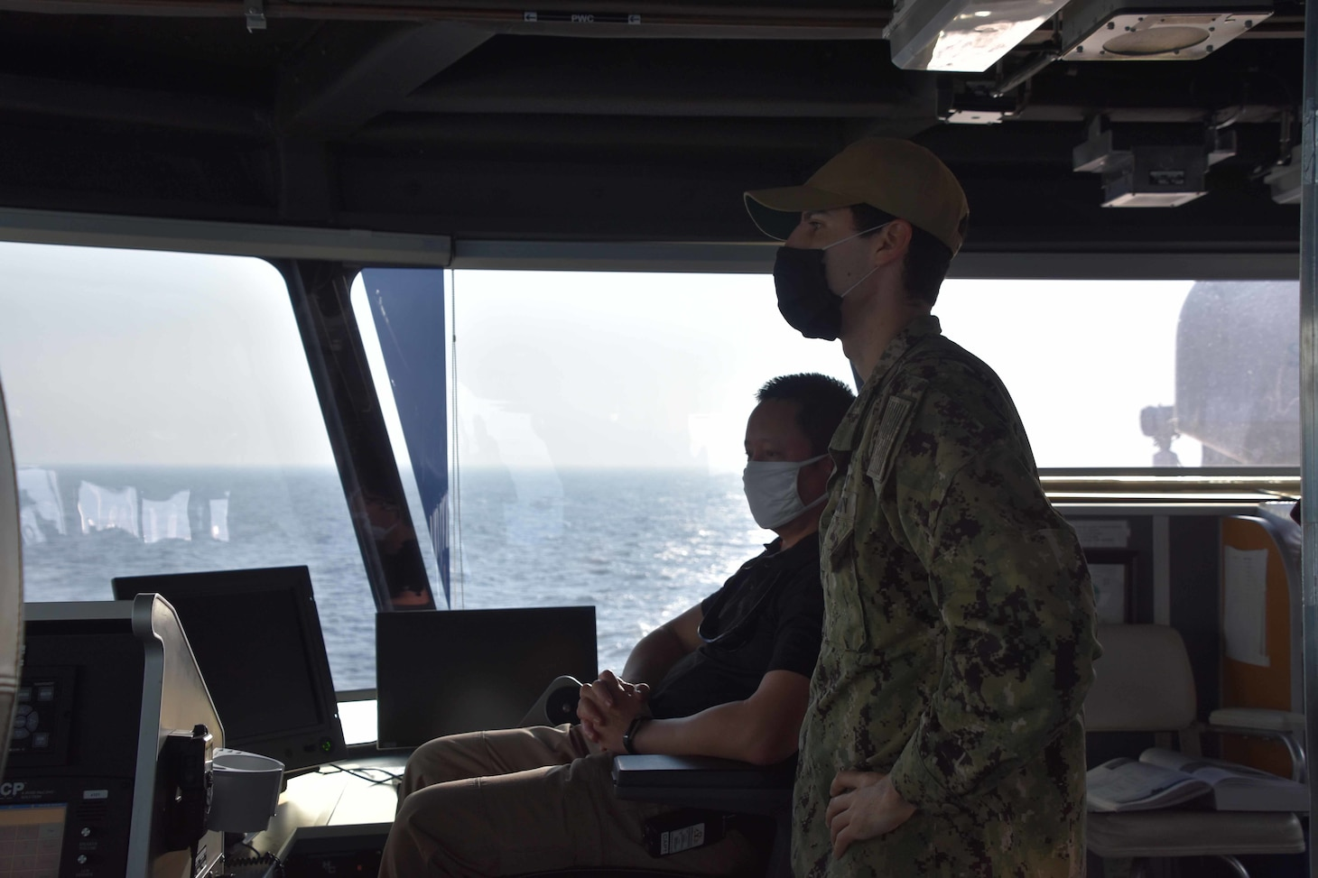 SNS Millinocket (T-EPF 3) Master Capt. Erwin Lao and Lt. Alexander Laabs, exercise lead from Destroyer Squadron 7, navigate from the bridge as ships from the Bangladesh Navy maneuver in formation during the sea phase of Cooperation Afloat Readiness and Training (CARAT) Bangladesh.