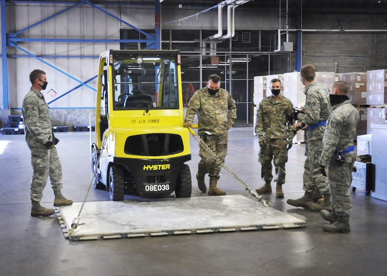 Airmen of the 87th Aerial Port Squadron use chains to restrain a 463L pallet (a standardized pallet used for transporting military air cargo). This challenge simulated tying down a vehicle on a C-17 Globemaster III and calculated the effectiveness angle of the chains. A forklift was backed up to the edge of the pallet, and the group was given two different angles and lengths to figure out the effective restraint that each chain would provide.
