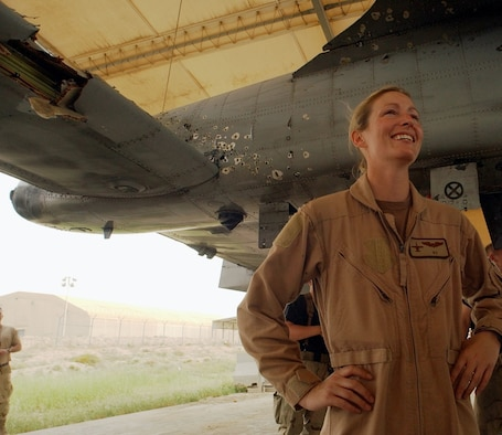 Col. Kim Campbell, Director of the Center for Character and Leadership Development, poses with her damaged A-10 Thunderbolt II after a 2003 combat mission in Iraq. Campbell is a 1997 graduate and command pilot with over 1,700 hours in the A-10.
