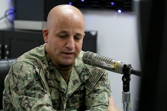 Master Chief Petty Officer of the Navy (MCPON) Russell Smith answers questions during an American Forces Network Bahrain radio show.