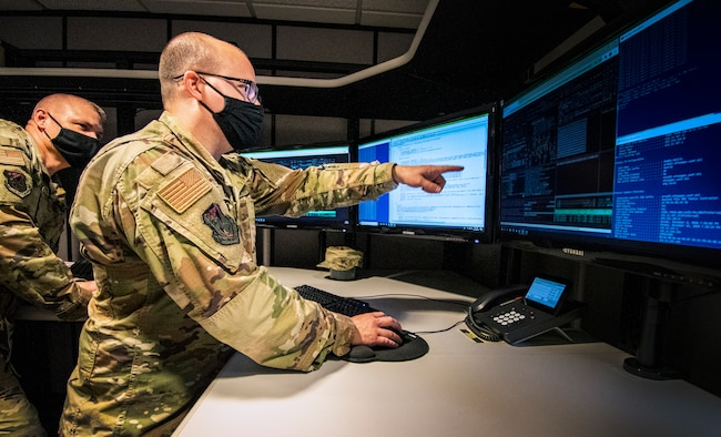 Tech. Sgt. Christopher Erhart, 190th Communications Flight IT technician (right), and Chief Master Sgt. Shawn Willard, 190th CF superintendent (left), prepare for the transition to the new Cyber Defense Mission the CF will be adapting in 2021.