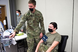 Airmen taking blood pressure.