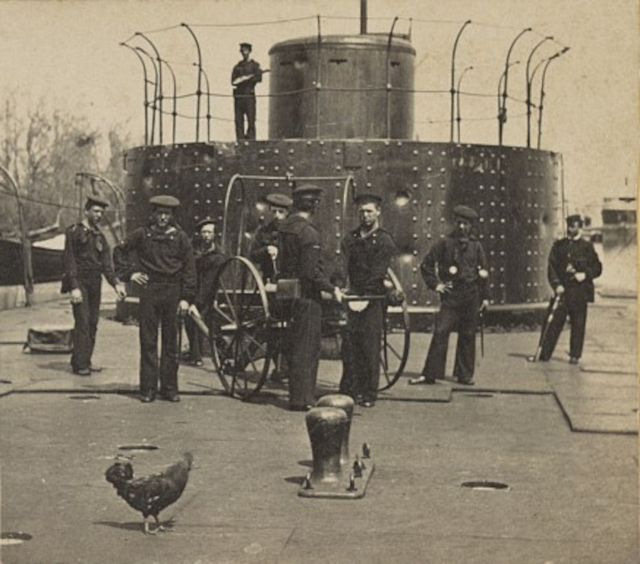 An old photo shows sailors standing in front of a turret on a ship.