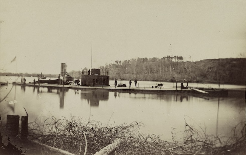 An ironclad Civil War ship's deck is visible just above the water level on a river.