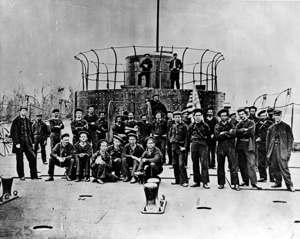 An old photo shows dozens of sailors posing near the turret of a ship.