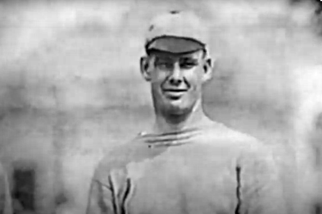 A man in a baseball player's uniform poses for a photo.
