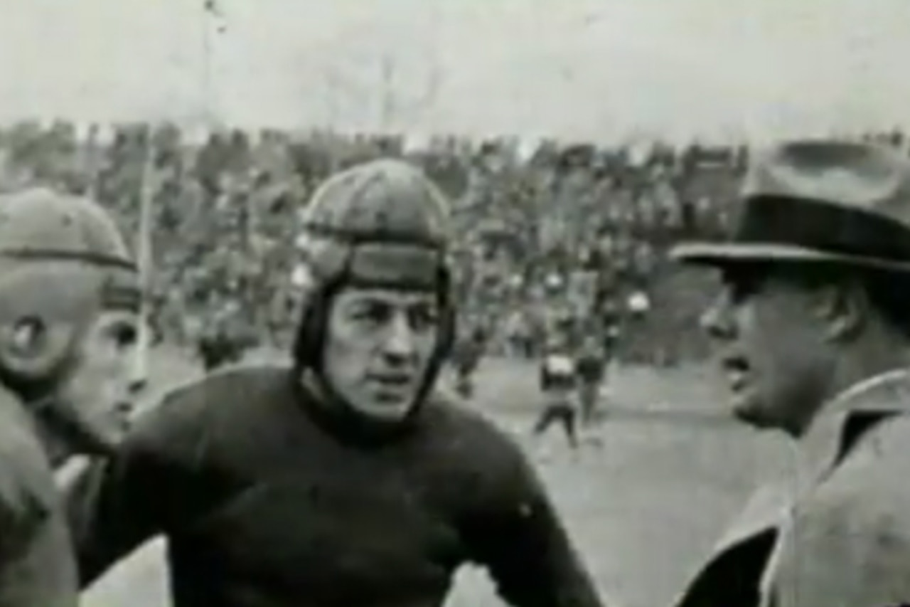 A man talks to football players during a game.