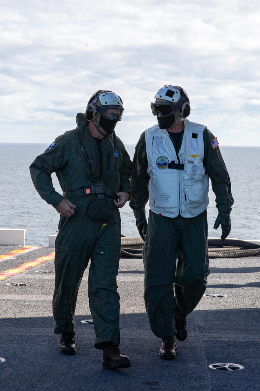 Rear Adm. Craig Claperton, commander, Carrier Strike Group (CSG) 12, left, walks with Capt. Jeremy Shamblee, USS Gerald R. Ford's executive officer, on the flight deck.